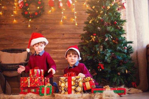 家でクリスマスプレゼントを開く男の子