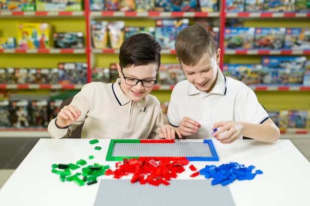 Boys play together with colored plastic blocks in the gaming center, school.