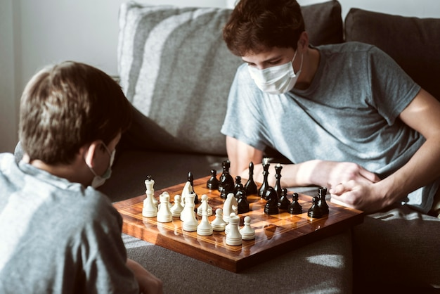 Boys playing chess at home while being quarantined