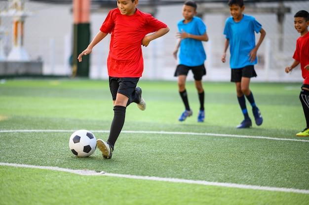 サッカー練習場でサッカーをしている男の子