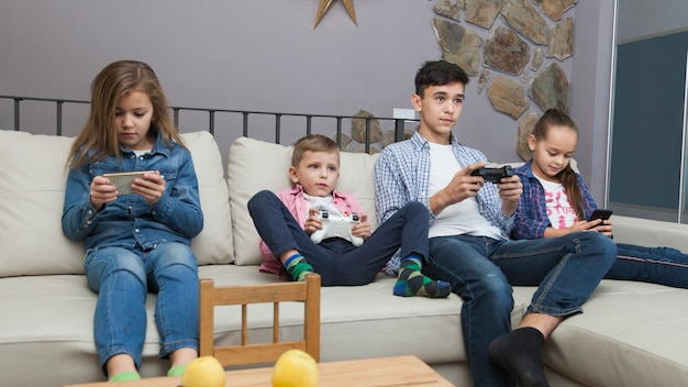 Boys playing video games and girls using smartphones