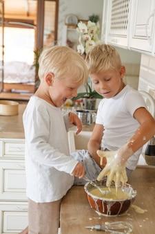 キッチンで自家製パイを焼く準備をしている男の子。二人の兄弟クッキ