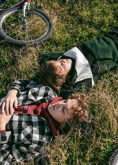 Boys resting on grass while riding their bikes