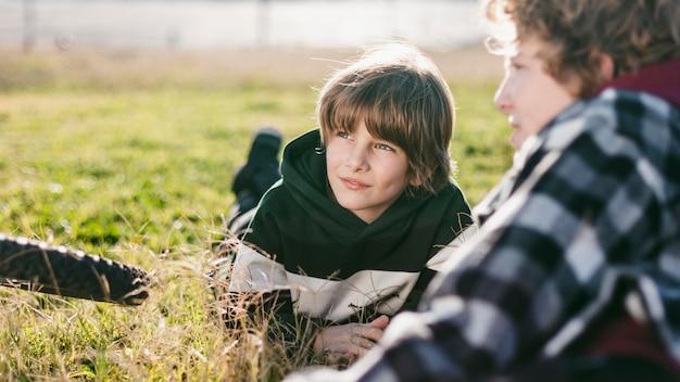 自転車に乗っている間草の上で休んでいる男の子