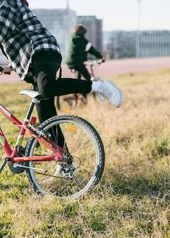 Мальчики катаются на велосипедах по траве на открытом воздухе