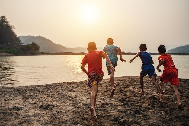 Мальчики бегают по воде и веселятся на озере
