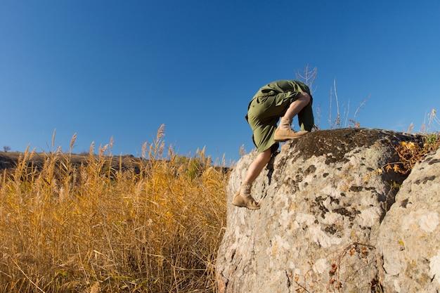 秋のシーズン中に青い空の下でブラウンフィールドの大きな古い岩に登るボーイズスカウト。