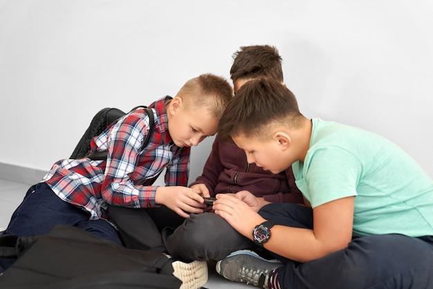 Мальчики сидят на полу и играют в игру на смартфоне.