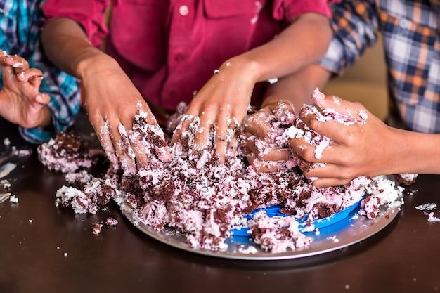 手でケーキを壊す男の子。 3人の子供の手がケーキを壊します。これで終わりです。私たちはできる限りのことをしました。