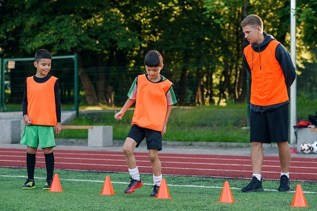 Boys training among plastic cones during football exercises at the stadium