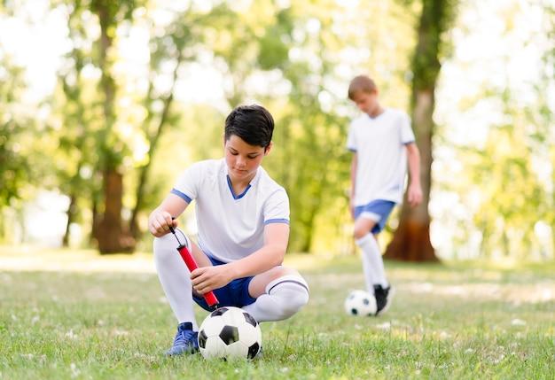 야외에서 축구 경기를 위해 훈련하는 소년