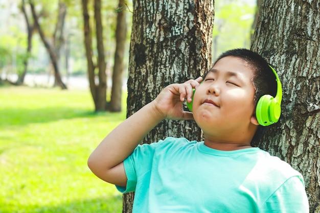 Boys wearing green music headphones standing against the tree, closed eyes, happy