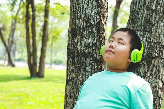 Boys wearing green music headphones standing against the tree, closed eyes, happy.