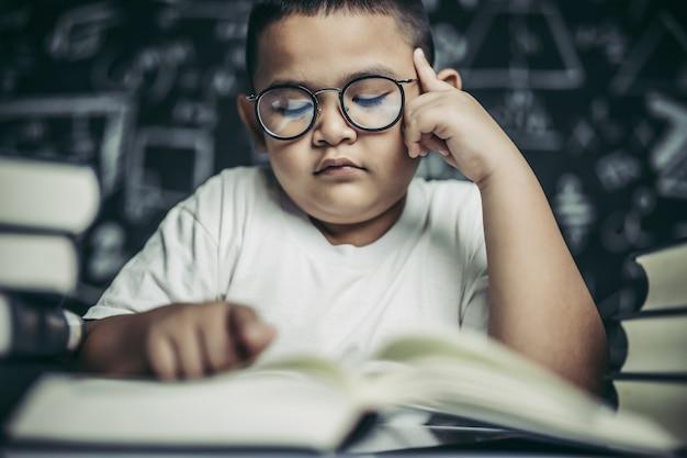 眼鏡をかけた男の子が本を書いて教室で考える