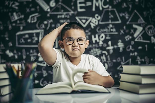 Мальчики в очках пишут книги и думают в классе