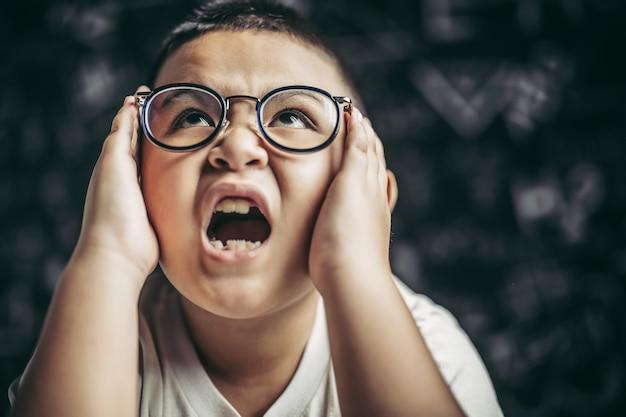 안경을 쓴 소년은 책을 쓰고 교실에서 생각합니다.