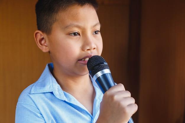 노래를 배우는 마이크를 가진 소년