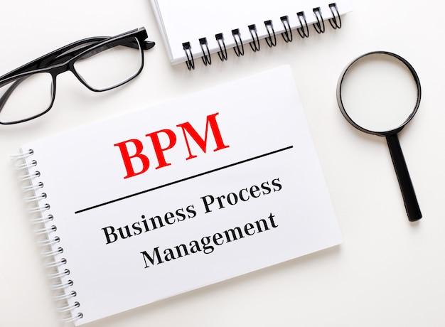 Bpm business process managementは、ノートブックの近くの明るい背景に白いノートブック、黒いフレームのメガネ、虫眼鏡で書かれています。
