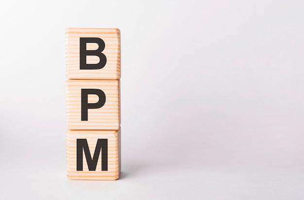 白い壁に柱状の木製ブロックのbpm文字、コピースペース