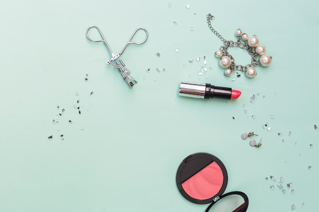 Bracelet; earrings lipstick; blusher and eyelash curlers on pastel backdrop