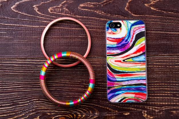 Браслет возле телефона смартфон и аксессуар на дереве соединение быта и техники, аксессуары т ...