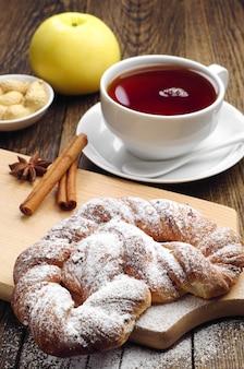 木製のテーブルに粉砂糖とお茶を入れた編みこみお団子