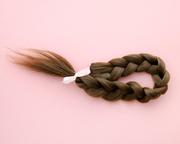 Braided hair with little pink ribbon