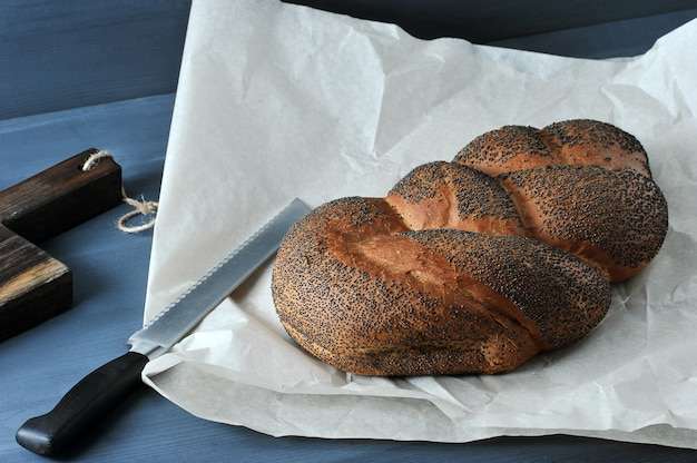 Braided loaf with poppy seeds on brown paper with a bread knife
