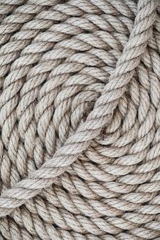 Плетеная толстая веревка перевязана мотком. пеньковая веревка для декора и дизайна. фон из рыболовной веревки.