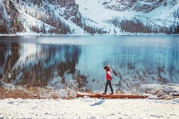 ドロミテの山湖braiesを歩いている女性とカラフルな冬の風景。