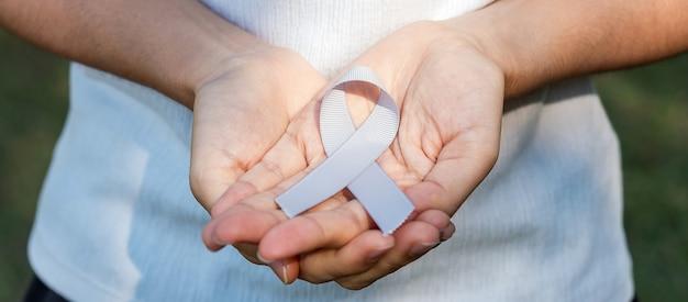 Месяц осведомленности рака мозга, рука женщины, держащая ленту серого цвета для поддержки людей, живущих. концепция здравоохранения и всемирного дня рака