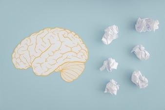 Brain cutout with white crumpled paper balls on gray background