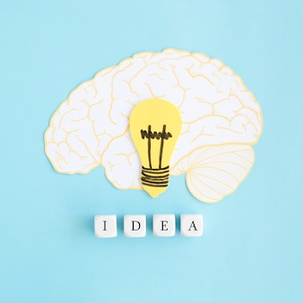 Brain and electric bulb paper cut out with white idea blocks on blue backdrop