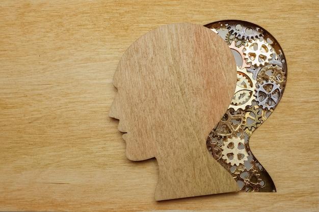 Концепция модели мозга из шестерен и зубчатых колес на деревянном