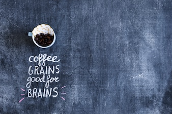 Brain paper cutout and coffee beans in cup with text on chalkboard