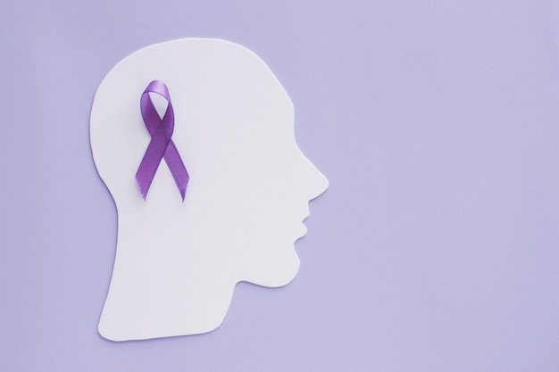 Brain paper cutout with purple ribbon on purple background, epilepsy and alzheimer awareness, seizure disorder, mental health concept