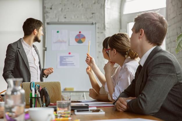 脳機能マッピング。会議をしている若いビジネス専門家のグループ。同僚の多様なグループが、新しい決定、計画、結果、戦略について話し合います。創造性、職場、ビジネス、財務、チームワーク。
