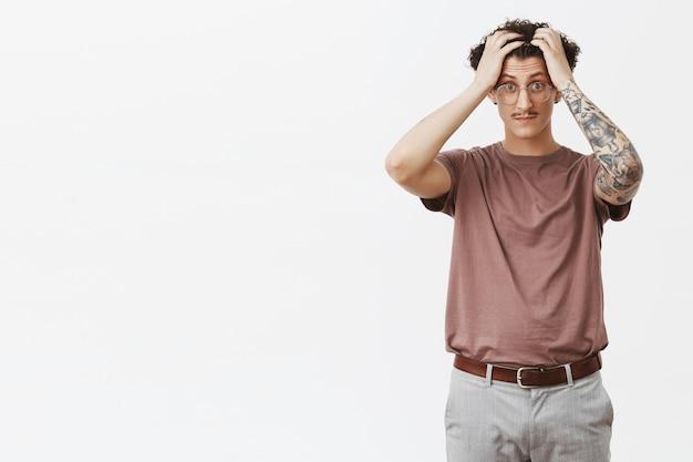 I cervelli ribollono da studenti stupidi. ritratto di turbato e scioccato stordito attraente giovane dai capelli ricci ragazzo con baffi divertenti e tatuaggi che toccano i capelli scoppiettanti occhi cercando sotto pressione e stressati