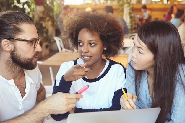 Brainstorm concept. man in glasses explaining ideas and vision to his female partners while having hot dispute on common project.