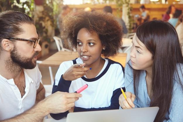 Concetto di brainstorming. uomo con gli occhiali che spiega idee e visione alle sue partner femminili mentre ha una controversia calda sul progetto comune.