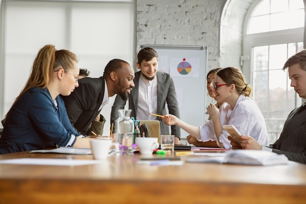 ブレーンストーミング。会議をしている若いビジネス専門家のグループ。同僚の多様なグループが、新しい決定、計画、結果、戦略について話し合います。創造性、職場、ビジネス、財務、チームワーク。