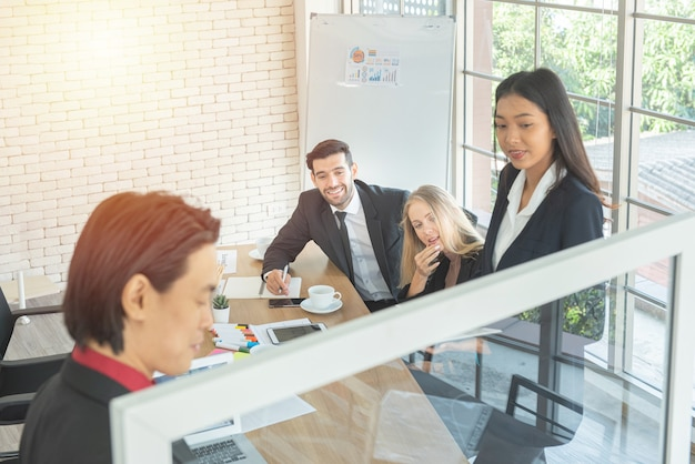 Мозговой штурм с бизнес-многоэтническими коллегами. азиатский деловой человек представляет диаграмму на стеклянной стене с бизнес-командой в офисе.