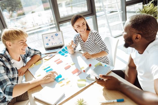 あなたのアイデアをブレインストーミングします。オフィスに座って一緒に働いている間彼らのプロジェクトについて話し合っている楽しい若い同僚の上面図