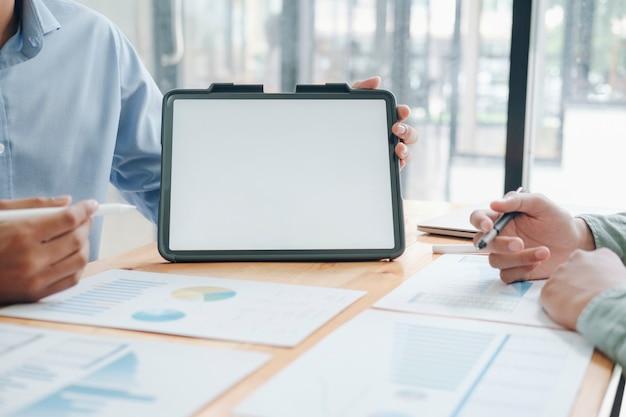 ブレーンストーミングとディスカッションプロセス。新しいスタートアッププロジェクトで働いている若いビジネスクルーの写真。空白の画面のタブレットを保持している男。