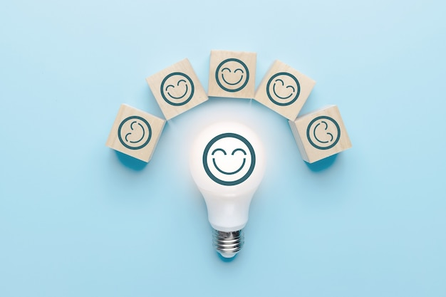 Brainstorming and creative idea team concept, light bulb with face of smiled icon and wood block on blue background