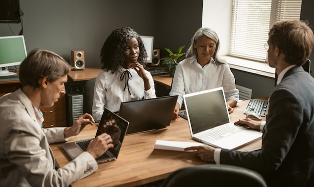 Brainstorming of diverse group employees working together on a new business project. young african girl, an elderly gray-haired asian woman and two caucasian young men share their ideas