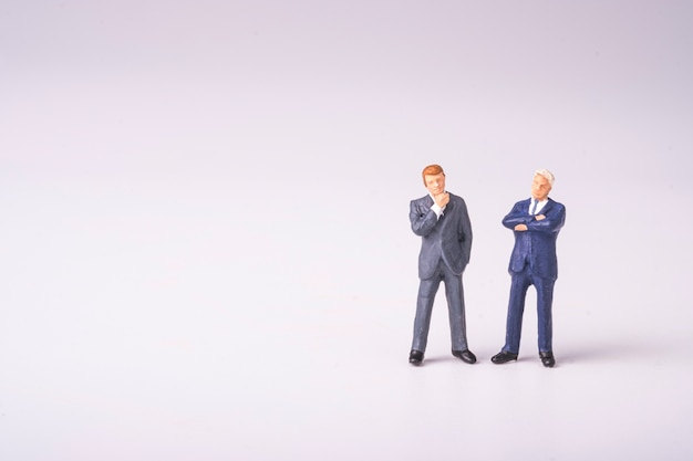 Мозговой штурм для новой концепции мышления бизнес-идеи, двух бизнесменов, миниатюрная фигура, стоя, разговаривает и обсуждает.