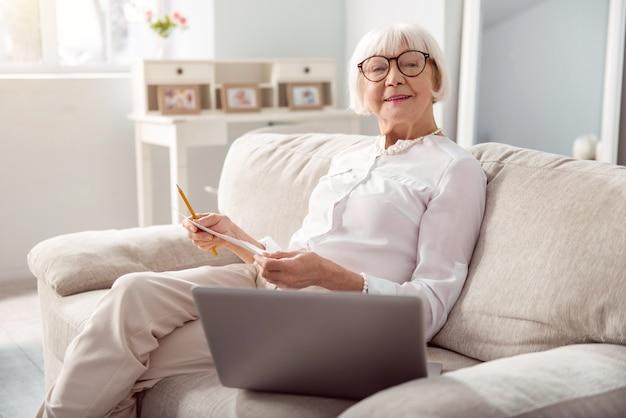 ブレーンストーミングのアイデア。ソファーに座ってポーズをとる魅力的な年配の女性がプロジェクト計画を策定し、下書きを紙に書きながらポーズをとる