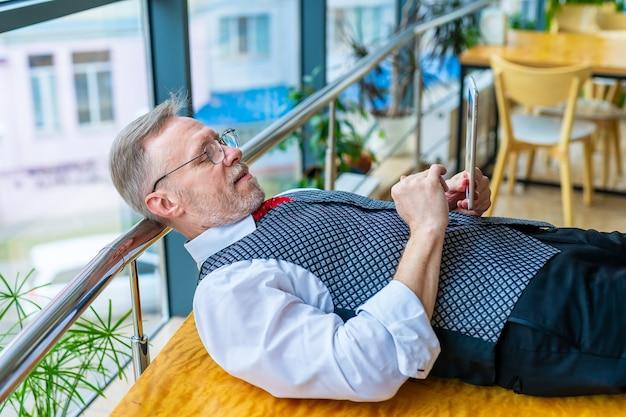브레인스토밍. 손에 태블릿 테이블에 누워 남자입니다. 인터넷에서 아이디어를 검색합니다. 비즈니스, 컴퓨터 작업, 원격 작업 프리랜서의 개념.