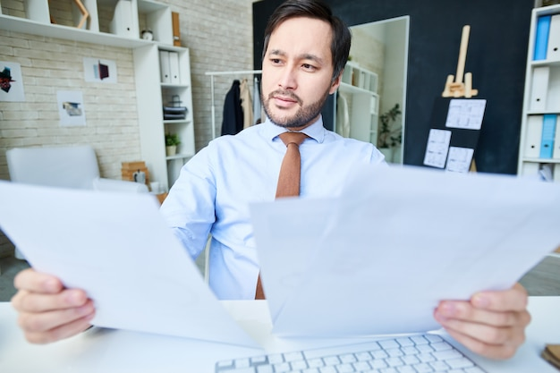 Brainstorming man with papers in office